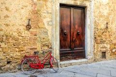 PIENZA, TUSCANY/ITALY - 19. MAI: Rotes Fahrrad, das an einem w sich lehnt Lizenzfreies Stockfoto