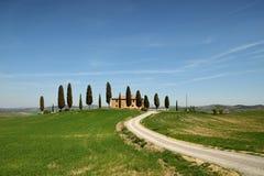 PIENZA, TUSCANY / ITALY - MAR 31, 2017: tuscany landscape, farmland I Cipressini, italian cypress trees with rural white road Stock Photo