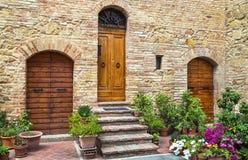 Pienza, Włochy †'Lipiec 22, 2017: Trzy drewnianego dzwi wejściowy w domu Typowi drzwi na kamiennej ścianie w Tuscany miasteczku Obraz Stock