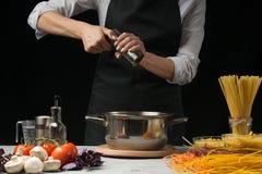 Pieprzowy młyn w szefie kuchni na czarnym tle Na stołowych warzywach, spaghetti, makaron, Włoski makaron Pojęcia kucharstwo obrazy stock