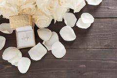 Pierścionek jest beside białe róże kwiat jest na drewnianym backgroun Obraz Stock