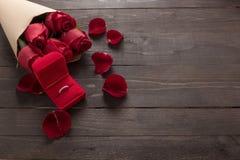 Pierścionek jest czerwone róże beside kwitnie na drewnianym tle Obrazy Royalty Free