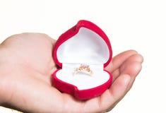 Pierścionek w otwartym pudełku w man& x27; s ręka propozycja - odizolowywa Fotografia Stock