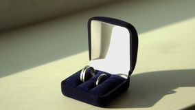 Pierścionek w pudełku na drewnianym stole zapas Obrączki ślubne w skrzynce na stole iluminującym światłem słonecznym zdjęcie wideo