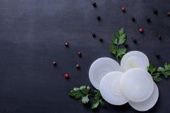 Pierścionki cią w białe cebule z ziele i pikantność na zmroku - błękitny tło Warzywa obraz stock