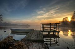 Pier. A pier at a lake a foggy morning with a boat Stock Photos