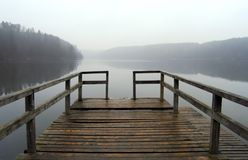 Pier. Lonely pier with rail on the foggy lake, tranquil autumn scenery Stock Photography