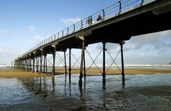 Pier. Long pier jutting out to sea at low tide Royalty Free Stock Photos