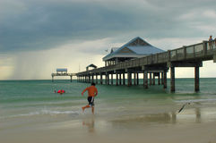 Pier. Long pier and beach in florida with running kid and thunderstorm stock photography