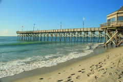 The pier. A wooden pier leading out into the ocean Royalty Free Stock Photo