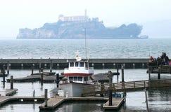 Pier 39 & Alcatraz. Pier 39 in San Francisco with a foggy view of Alcatraz in the background Stock Photo
