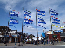 Pier 39 Flags wave as people check out booths Royalty Free Stock Images