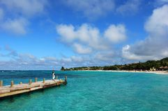 On The Pier. The view of a Roatan island beaches with a girl standing on a wooden pier (Honduras Stock Photography