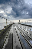 Pier. A brroding sky against a converging pier Royalty Free Stock Photo