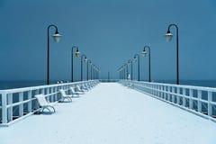 Pier abgedeckt mit Schnee Snowy, schwermütiges Wetter Stockfotografie
