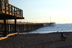 Pier Afternoon. A woman sits on a bench enjoying the afternoon at the Ventura Pier in California Stock Image