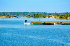 Pier in archipelago. Concrete pier in the Swedish archipelago. Small boats moored alongside pier. Calm, still water. Islands in background. Blue sky and sea stock image