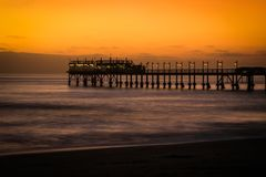 Pier on the Atlantic Ocean in Swakompund, Namibia. Beautiful sunset with a bright sky and soft gentle water stock images