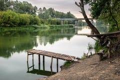 Pier auf einem ruhigen Fluss im Sommer Hölzerne Pierbrücke lizenzfreie stockbilder