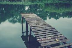 Pier auf einem ruhigen Fluss im Sommer Hölzerne Pierbrücke lizenzfreie stockfotografie