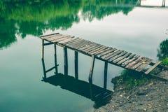 Pier auf einem ruhigen Fluss im Sommer Hölzerne Pierbrücke stockbild