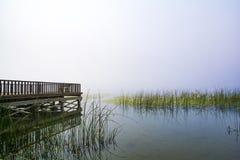 Pier auf nebeligem See Lizenzfreies Stockfoto