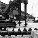 Pier Auger and Heavy Equipment. A black and white image of some heavy construction equipment on one of the piers in Seattle port, this includes giant drill bits Stock Image
