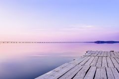 Pier on the background of the sea with a glossy surface, which reflects the pink-blue sky. The pier is made of old gray wood. The sky is painted in pastel pink royalty free stock images