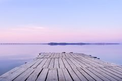 Pier on the background of the sea with a glossy surface, which reflects the pink-blue sky. The pier is made of old gray wood. The sky is painted in pastel pink royalty free stock photography