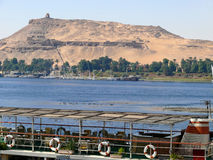 Pier on the bank of the Nile in Aswan, on a background of ancien Royalty Free Stock Images