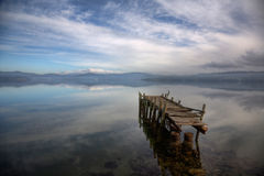 Pier at beach. A derelict pier against a moody evening sky royalty free stock photography