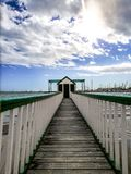 Pier at the beach against seascape and cloudy sky stock photos