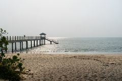 A pier on a beach leading into the ocean royalty free stock photography
