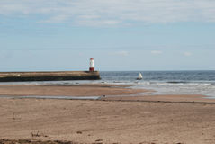 Pier and beach with old sailing yacht at Berwick-upon-Tweed. Lighthouse, beach and old sailing yacht at Spittal Stock Images