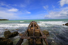 Pier at the beach at Ujung Kulon Indonesia. Tropical beach and pier at Ujung Kulon Indonesia with blue sky and white sandy beach Stock Photo