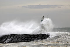 Pier and beacon covered by sea waves Royalty Free Stock Images