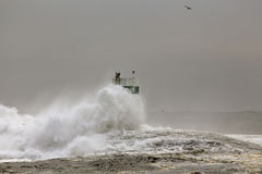Pier and beacon covered by sea waves Stock Photography