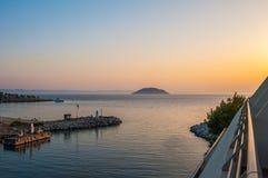 Pier bei Sonnenuntergang, Wasser auf dem Meer von einem Hügel, die Bootssegel auf dem Meer stockfotografie