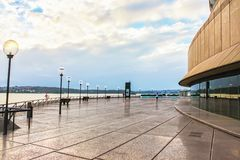 The pier at Bennelong Point in Circular Quay in Sydney Austraia - a woman runs beside the Opera House on a rainy morning. The pier at Bennelong Point in Circular stock image