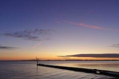 Pier bevor Sonnenaufgang mit dem kleinen Kran silhouettiert gegen den Morgenhimmel und roten die Kondensstreifenunkosten stockbild