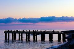 Pier on the Black Sea coast, Sochi, Russia. Silhouettes of fishermen with fishing rods on the pier on the background of a twilight sunset pink color on the Stock Photography