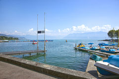 A pier and blue catamarans in Geneva lake bay harbor in Lausanne Royalty Free Stock Photography