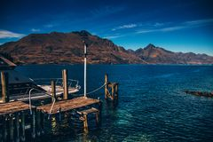 Pier on blue lake among mountains stock photography
