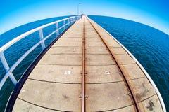 Pier in blue ocean water with fisheye horison. A pier in blue ocean water with fisheye horison in Basselton jetty Royalty Free Stock Image