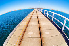 Pier in blue ocean water with fisheye horison Royalty Free Stock Image
