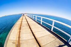 Pier in blue ocean water with fisheye horison. A pier in blue ocean water with fisheye horison in Basselton jetty Stock Photography