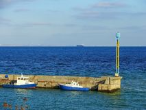 The pier in the blue sea, near which are the boats. The concrete pier in the blue sea, near which boats are attached, are on the horizon in the roadside cargo Royalty Free Stock Image
