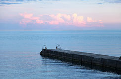 Pier, blue sky and sea on sunset Stock Images