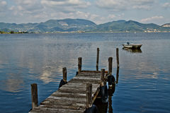 Pier and boat. Wooden pier and boat on Lake Massaciuccoli. Lucca Tuscany, Italy Royalty Free Stock Images