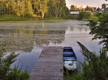 Pier with a boat on a quiet pond. Pier with a boat on the shore of a quiet pond, surrounded by forest vegetation. Reflections of trees in the water. Sunny stock photography